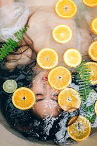 Woman bathes in bath with sliced fruit to improve her skin