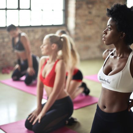 Five girls on pink yoga mats waiting for an exercise class to start