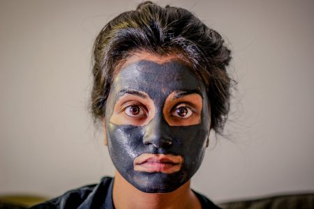 Woman with charcoal face mask on to improve her skin