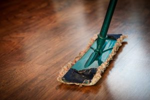 Shiny wood floors undergoing spring leaning with a mop