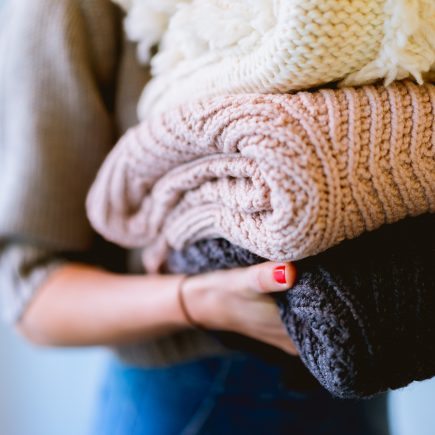 Woman spring cleaning and carrying old jumpers to donate to charity