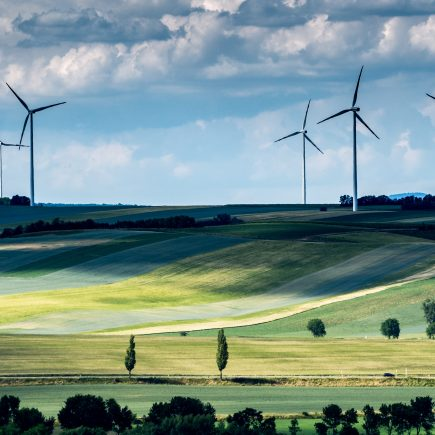 A wind farm in the distance after a landscape of green fields and trees which are not eligible for the Renewable Heat Incentive Scotland