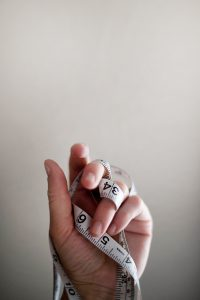 Hand with measuring tape wrapped around it to be used for non-surgical facelift Glasgow