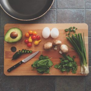 Raw healthy vegetables cut up on a wooden chopping board with a knife beside them