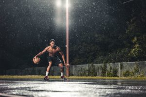 Man playing basketball in the rain for exercise