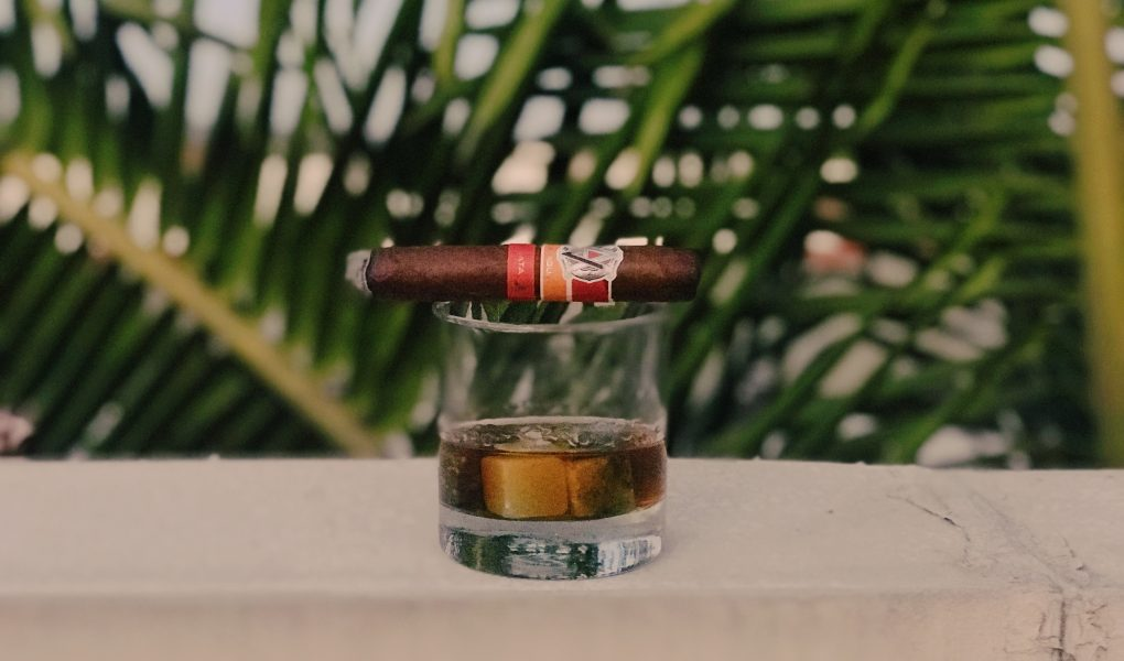 Rare Whisky in a glass on a ledge with a cigar laid across the top.