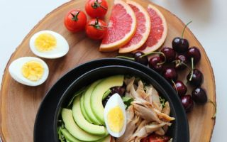 Plate of fruit, eggs, vegetables and chicken as part of a healthy diet